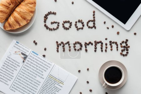 Photo for Top view of cup of coffee and good morning lettering made of coffee beans on white surface with croissants, newspaper and tablet - Royalty Free Image
