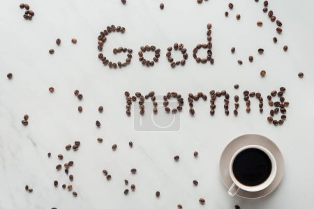 Photo for Top view of cup of delicious coffee and good morning lettering made of coffee beans on white marble - Royalty Free Image