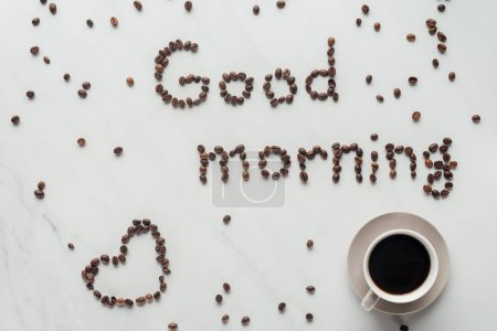 Photo for Top view of cup of coffee and good morning lettering made of coffee beans on white marble - Royalty Free Image