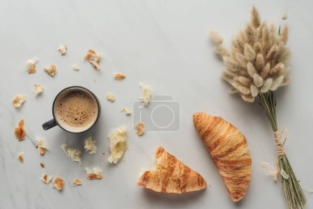 Photo for Top view of cup of coffee with croissants and bouquet of bunnytail ears on white marble - Royalty Free Image