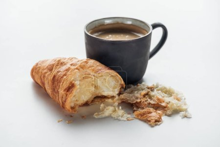 Photo for Close-up shot of coffee cup and bitten croissant on white - Royalty Free Image