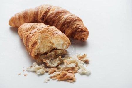 close-up shot of delicious bitten croissants on white surface