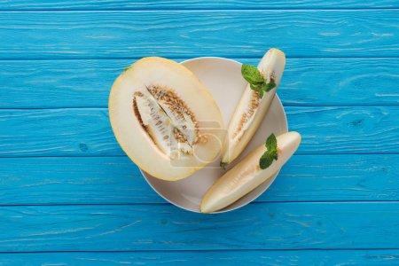 Photo pour Vue de dessus du melon sucré tranché mûr avec menthe sur plaque sur une surface en bois bleu - image libre de droit