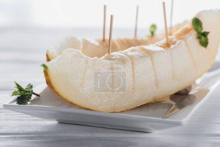 Photo pour Vue rapprochée du melon mûr sucré tranché avec menthe sur assiette - image libre de droit