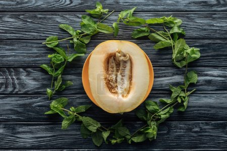 Photo for Top view of fresh ripe sweet melon and fresh mint on wooden surface - Royalty Free Image