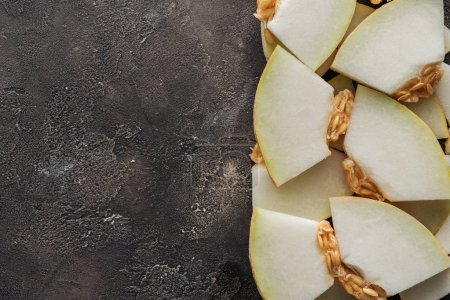 Photo for Top view of sliced sweet ripe honeydew melon on black grunge background - Royalty Free Image