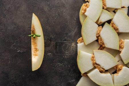 Photo pour Vue de dessus des tranches de melon mûr sucré sur fond grunge noir - image libre de droit