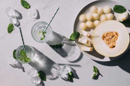 top view of sweet melon balls, half of ripe melon and refreshing beverage with mint and drinking straws in glasses on white