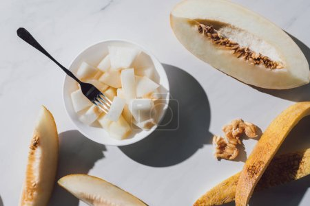 top view of sweet ripe sliced melon and seeds on white
