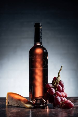 bottle of red wine, piece of delicious cheese and grapes on grey