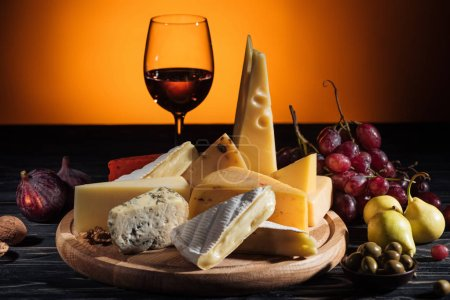 Photo for Different types of cheeses, glass of wine and fruits on table on orange - Royalty Free Image