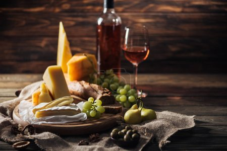 different types of cheeses, grapes and pears on rustic tablecloth