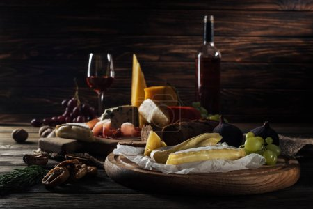 Different types of cheeses and fruits on cutting b...