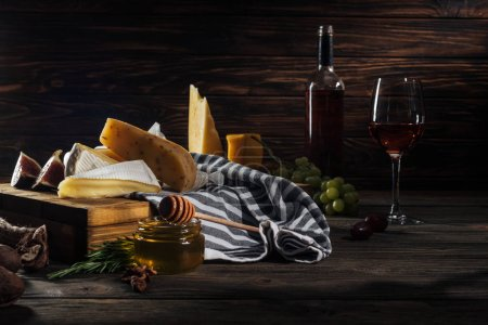 Photo for Different types of cheeses, honey with stick and wine on table - Royalty Free Image