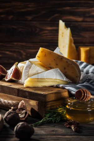 Photo for Different types of cheeses, honey and fig on table - Royalty Free Image