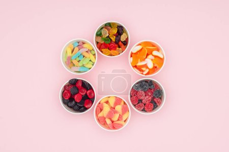 top view of paper cups with yummy jelly candies in circle isolated on pink