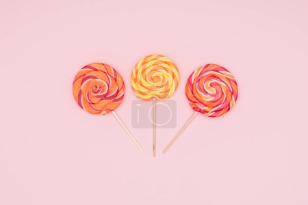 top view of three round yummy lollipops isolated on pink