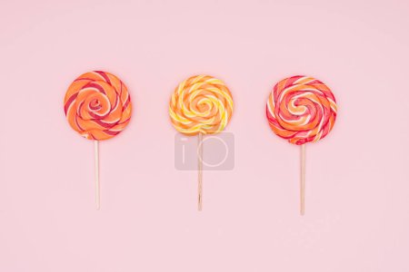 top view of three round lollipops isolated on pink