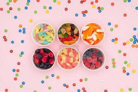 Foto de Vista elevada de vasos de papel con caramelos de la jalea deliciosa y dragee disperso aislados en rosa - Imagen libre de derechos