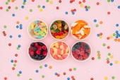 elevated view of paper cups with tasty jelly candies and scattered dragee isolated on pink