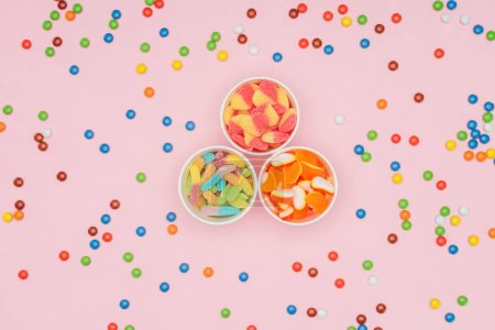 top view of paper cups with jelly candies and scattered dragee isolated on pink