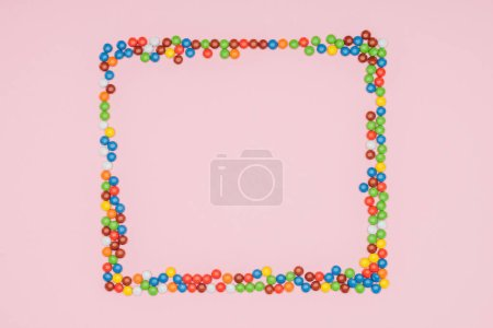 top view of frame of dragee candies isolated on pink