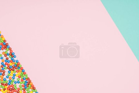 top view of yummy dragee candies on turquoise and pink surface
