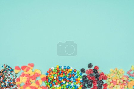 Photo for Top view of different colored sweets isolated on turquoise - Royalty Free Image