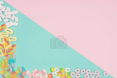 top view of jelly candies and marshmallows on turquoise and pink surface