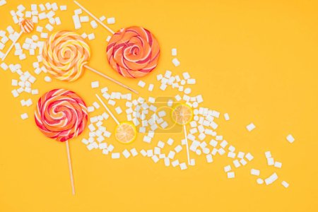 top view of scattered marshmallows and lollipops isolated on orange