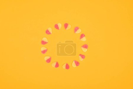 Photo for Top view of circle of jelly candies in shape of hearts isolated on orange - Royalty Free Image