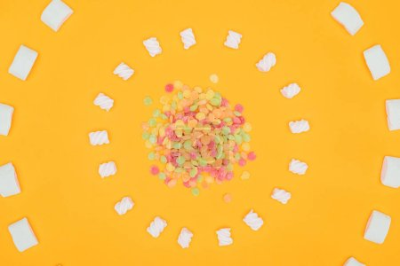top view of circles of jelly candies and marshmallows isolated on orange