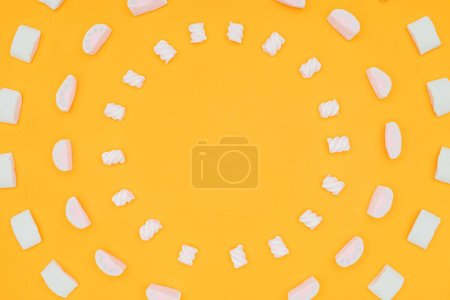 top view of circles of yummy marshmallows isolated on orange
