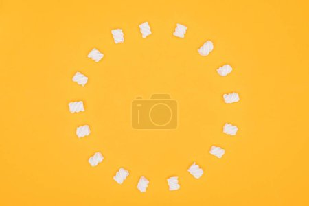 top view of circle of marshmallows isolated on orange
