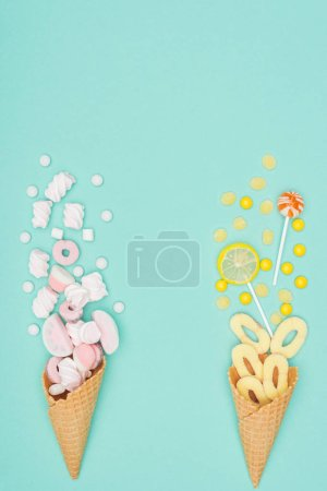 top view of marshmallows, lollipops and waffle cones isolated on turquoise