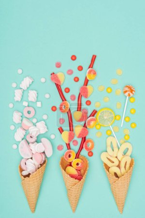 top view of jelly candies, marshmallows, lollipops and waffle cones isolated on turquoise