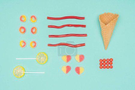 flat lay of jelly candies, dragee, lollipops and waffle cone isolated on turquoise