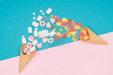 top view of jelly candies, marshmallows and waffle cones on blue and pink surface