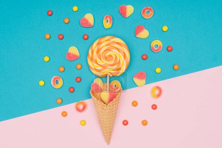 top view of jelly candies, lollipop and waffle cone on blue and pink surface