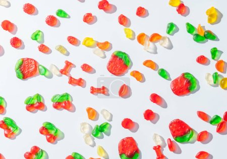elevated view of tasty scattered jelly candies on white