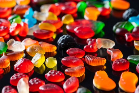 different colored jelly candies on black surface