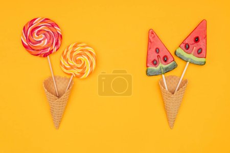 top view of yummy lollipops in waffle cones isolated on orange