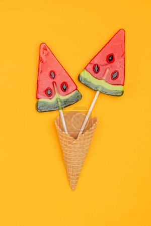 Photo for Top view of tasty lollipops in shape of watermelon in waffle cone isolated on orange - Royalty Free Image