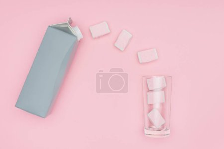 top view of marshmallows, glass and carton package isolated on pink