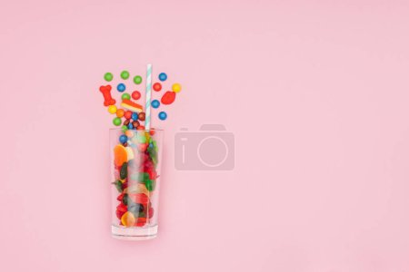 Photo for Top view of glass with jelly and dragee candies isolated on pink - Royalty Free Image
