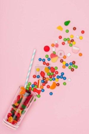 Foto de Vista superior de caramelos de jalea y dragee dispersos, vidrio y plástico paja aislado en rosa - Imagen libre de derechos