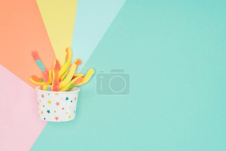 Photo for Top view of yummy jelly candies in paper container on colored surface - Royalty Free Image