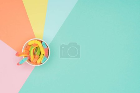 Photo for Top view of jelly candies in paper container on colored surface - Royalty Free Image