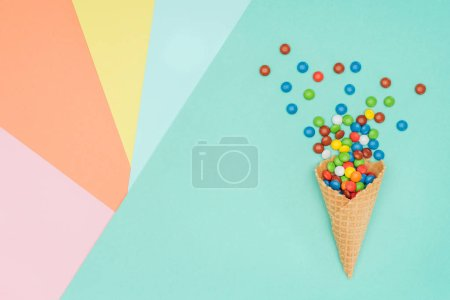 top view of scattered bright dragee candies and waffle cone on colored surface