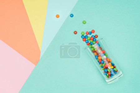 top view of scattered sweet dragee candies and glass on colored surface